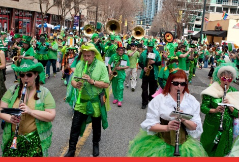 Atlanta, GA, USA - March 15, 2014:  A band dressed in eclectic green costumes plays while marching in the St. Patrick's parade down Peachtree Street.  (Atlanta, GA, USA - March 15, 2014:  A band dressed in eclectic green costumes plays while marching