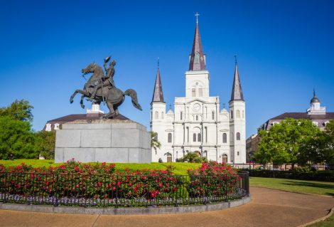 St. Louis Cathedral, Jackson Square, Louisiana, United States. Color horizontal image with Andrew Jackson statue in foreground with red flowers.