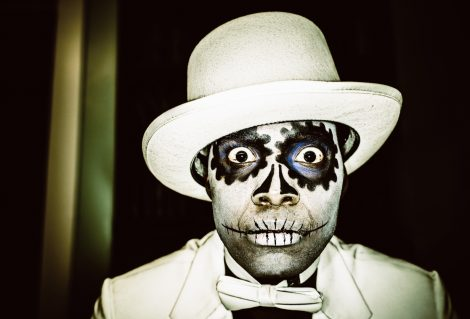 Man with typical Mexican-style Day of the Dead (Dia de los Muertos), sugar skull make-up, dressed in white suit and hat. Dark, Surreal Portrait.