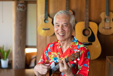 A front view portrait of an older Japanese man in a Hawaiian shirt playing his ukulele near a wall of instruments.