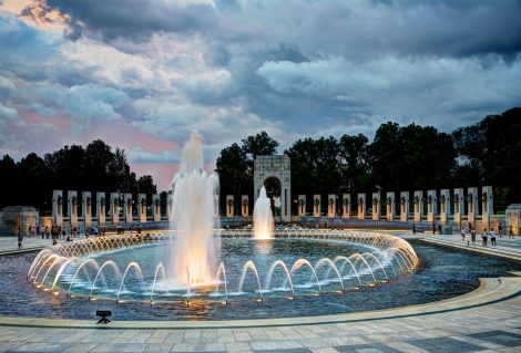 A photograph of the World War II Memorial at sunset. The Memorial is located on the National Mall in Washington, DC and is the first national memorial dedicated to all who served during World War II. It is located on 17th Street, between Constitution and Independence Avenues, and is flanked by the Washington Monument to the east and the Lincoln Memorial to the west. This photo was taken at sunset.