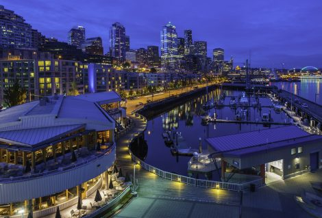 High angle view over the night lights and crowded cityscape of the Seattle waterfront, from the marina and luxury condominiums past the skyscrapers of downtown to the aquarium and ferry docks of Puget Sound, Washington, USA. ProPhoto RGB profile for maximum color fidelity and gamut.