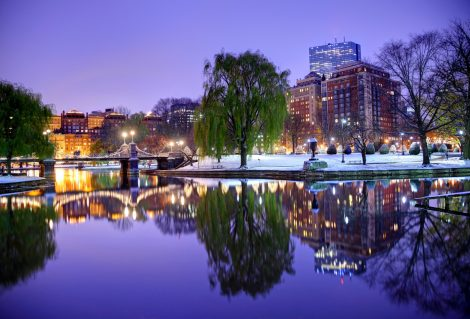 Boston's Back Bay neighborhood reflecting on a small pond in the Boston Public Garden. The Public Garden, also known as Boston Public Garden, is a large park located in the heart of Boston, Massachusetts, adjacent to Boston Common and is the first public garden in the United States.